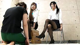 Two sensual Japanese girls work their sexy feet on a cock
